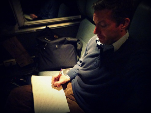 Andreas Moser writing on the train